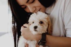 Mujer que lleva a cabo el dogt adorable adolescente femenino con el animal doméstico en casa P Fotos de archivo