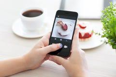 Mujer que lleva a cabo el espacio del iPhone 6 gris con el servicio Instagram Imagen de archivo libre de regalías