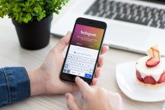 Mujer que lleva a cabo el espacio del iPhone 6 gris con el servicio Instagram Fotos de archivo libres de regalías