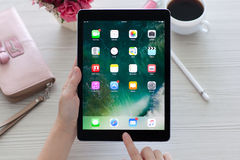 Mujer que lleva a cabo el favorable espacio del iPad gris con IOS 10 del papel pintado Imagenes de archivo