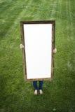 Mujer que lleva a cabo el marco rectangular en blanco Imagen de archivo