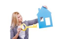 Mujer que lleva a cabo el modelo y la llave de papel de la casa Fotografía de archivo