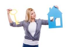 Mujer que lleva a cabo el modelo y la llave de papel de la casa Foto de archivo