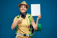 Mujer que lleva a cabo el pequeño tablero de la muestra y que muestra el pulgar para arriba Imágenes de archivo libres de regalías