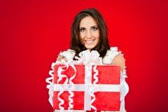 Mujer que lleva a cabo el regalo de Navidad grande Imagenes de archivo