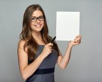 Mujer que lleva a cabo el tablero de la muestra y que señala con la pluma Fotografía de archivo libre de regalías