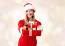 Mujer que lleva a cabo hacia fuera los regalos de Navidad que dan alcohol de la Navidad fotografía de archivo libre de regalías