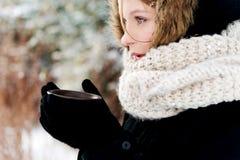 Mujer que lleva a cabo la bebida caliente al aire libre Foto de archivo libre de regalías