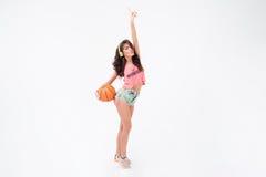Mujer que lleva a cabo la bola del baloncesto y la música que escucha en auriculares Imagenes de archivo