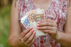 Mujer que lleva a cabo la cuenta euro en sus manos Imagen de archivo