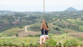 Mujer que lleva a cabo la cuerda la silla del oscilación y jugar feliz las montañas del fondo en el parque eólico en Khao Kho, Ph metrajes