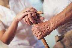 Mujer que lleva a cabo la mano del viejo hombre con el bastón Imagenes de archivo