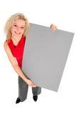 Mujer que lleva a cabo la muestra en blanco Imagen de archivo