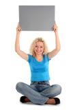 Mujer que lleva a cabo la muestra en blanco Imagen de archivo libre de regalías