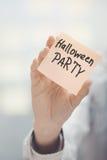 Mujer que lleva a cabo la nota adhesiva con el texto del partido de Halloween Imagenes de archivo