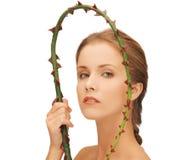 Mujer que lleva a cabo la rama con las espinas imagen de archivo libre de regalías