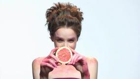 Mujer que lleva a cabo la rebanada del pomelo almacen de metraje de vídeo