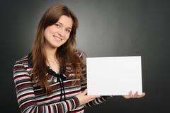 Mujer que lleva a cabo a la tarjeta blanca vacía Fotografía de archivo libre de regalías