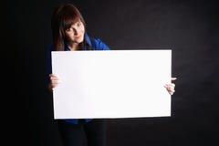 Mujer que lleva a cabo a la tarjeta en blanco en fondo negro. Fotos de archivo libres de regalías