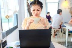 Mujer que lleva a cabo la taza de establecimiento de una red social del uso del café con el ordenador portátil Imagen de archivo