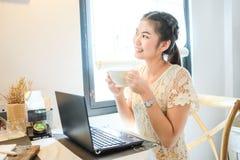 Mujer que lleva a cabo la taza de establecimiento de una red social del uso del café con el ordenador portátil Fotografía de archivo