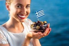 Mujer que lleva a cabo las aceitunas griegas Fotos de archivo libres de regalías