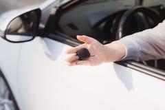 Mujer que lleva a cabo las llaves de ignición de un coche en su mano que las cuelga a través de la ventana lateral abierta imagen de archivo libre de regalías