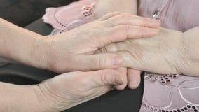 Mujer que lleva a cabo las manos arrugadas flácidas de la mujer mayor metrajes