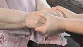 Mujer que lleva a cabo las manos arrugadas flácidas de la mujer mayor almacen de video