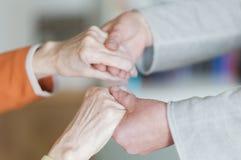 Mujer que lleva a cabo las manos del mujeres mayores Fotografía de archivo