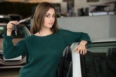 Mujer que lleva a cabo llave del coche dentro de la concesión de coche Imagen de archivo libre de regalías