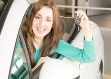 Mujer que lleva a cabo llave del coche dentro de la concesión de coche Imagenes de archivo