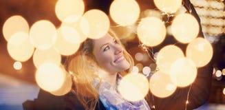 Mujer que lleva a cabo luces de hadas de la Navidad en la noche al aire libre en primer de la ciudad foto de archivo libre de regalías