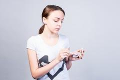 Mujer que lleva a cabo maquillaje contra Gray Background Fotografía de archivo