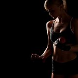 Mujer que lleva a cabo pesas de gimnasia rojas Imagen de archivo libre de regalías