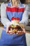 Mujer que lleva a cabo relevo de la nuez, de la miel y de los frutos secos Imagen de archivo libre de regalías