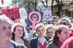 Mujer que lleva a cabo símbolo femenino rosado en marzo Imagen de archivo libre de regalías