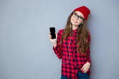 Mujer que lleva a cabo smartphone y música que escucha en auriculares Fotografía de archivo libre de regalías