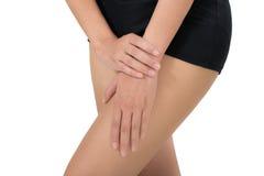 Mujer que lleva a cabo su cuerpo sano hermoso con el masaje del muslo en área del dolor Fotografía de archivo