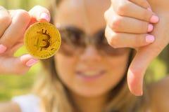 Mujer que lleva a cabo un bitcoin de oro y que muestra los pulgares abajo Imagenes de archivo