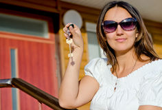 Mujer que lleva a cabo un clave de la puerta de la casa Foto de archivo libre de regalías