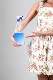 Mujer que lleva a cabo un espray detergente Fotos de archivo libres de regalías
