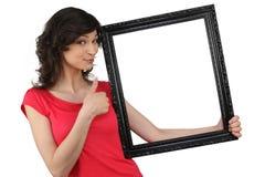 Mujer que lleva a cabo un marco Foto de archivo