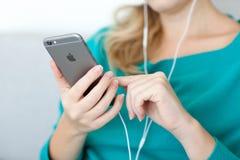 Mujer que lleva a cabo un nuevo espacio del iPhone 6 gris foto de archivo