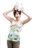 Mujer que lleva a cabo un piggybank sobre su cabeza fotos de archivo