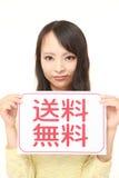 Mujer que lleva a cabo a un tablero de mensajes con el ENVÍO GRATIS de la frase en KANJI Fotografía de archivo libre de regalías