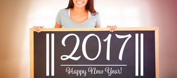 mujer que lleva a cabo a un tablero negro con el texto del Año Nuevo Imagen de archivo libre de regalías