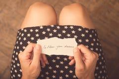 Mujer que lleva a cabo un trozo de papel con un mensaje Fotografía de archivo libre de regalías