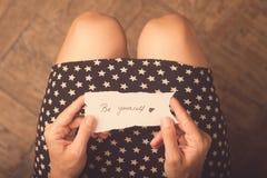 Mujer que lleva a cabo un trozo de papel con un mensaje Imagen de archivo