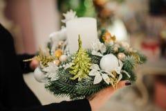 Mujer que lleva a cabo una composición de la Navidad hecha del árbol de abeto adornado con la vela, las bolas de cristal y el árb foto de archivo